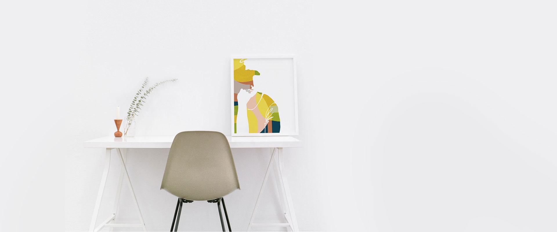 Bild eines Schreibtisches an einer weißen Wand mit einem Stuhl davor. Auf dem Schreibtisch steht ein großer Bilderrahmen mit einer Illustration von einer Frau.