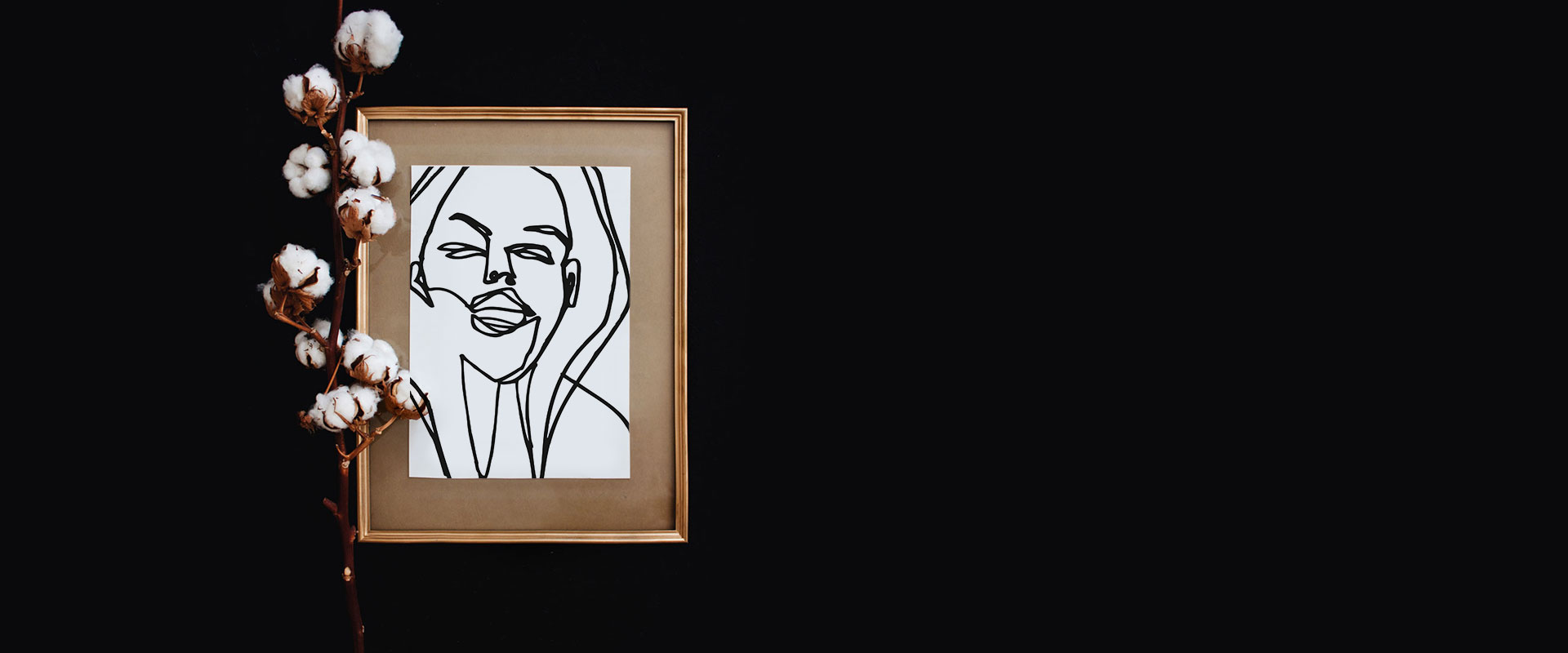 Schwarzer Hintergrund auf dem ein goldener Bilderrahmen mit einer Baumwollpflanze liegt. Im Bilderrahmen ist eine schwarz/weiße one line illustration einer lachenden Frau zu sehen.
