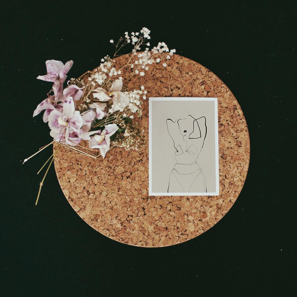 Postkarte liegt auf einem runden Korktablet mit Blumen daneben. Postkarte zeigt filigrane one line illustration einer nakten Frau.