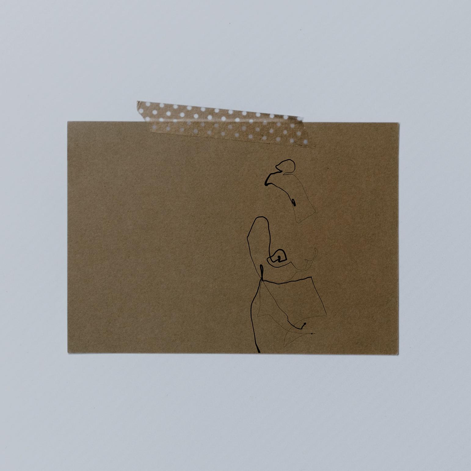 Postkarte aus Kraftkarton mit Tape an der Wand befestigt. Postkarte zeigt filigrane one line illustration einer nakten Frau