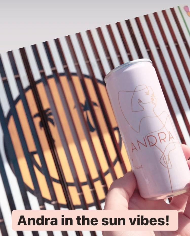 Andra in the sun vibes! Weindose wird in die Sonne gehalten vor einem großen Smiley an der Wand.